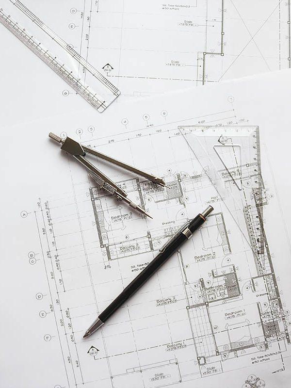 byggritningar framför en snickare på en byggfirma